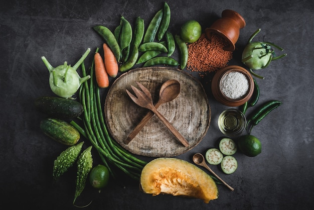 Vegetables on a black table with wooden board in the middle