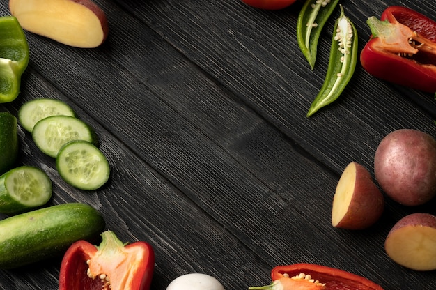 Vegetables on a black wooden table , top view and with copy space in center
