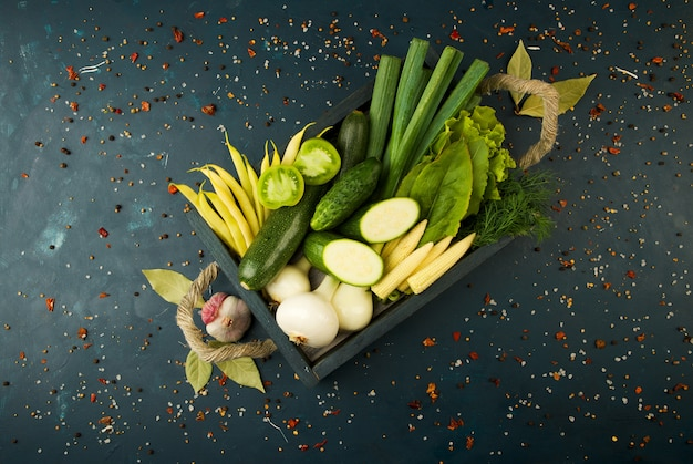 The vegetables in the box on the stone a dark. young herbs onions garlic green beans yellow corn zucchini bright spices are in a wooden box with rope handles on a dark textured.