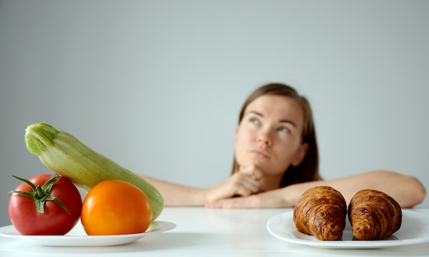 Vegetables and croissants on white table and woman with puzzled sight on background.
