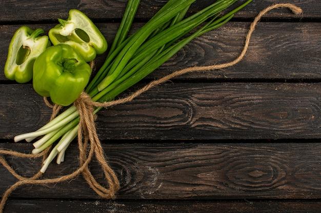 Le verdure hanno tagliato i peperoni dolci verdi insieme alle erbe verdi legate su uno scrittorio di legno rustico marrone