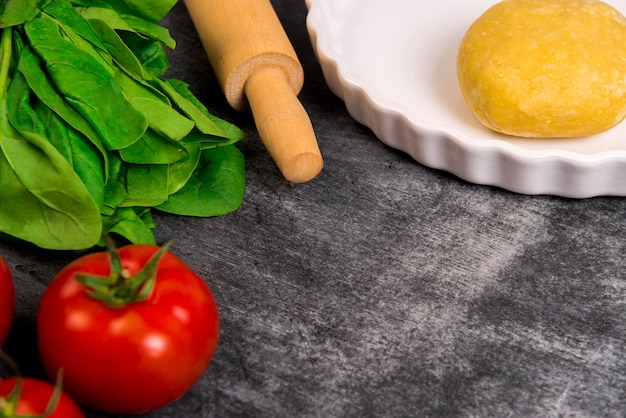 Vegetables and dough over grey wooden surface