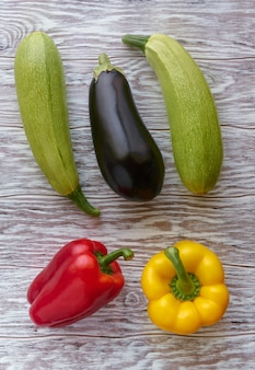 Vegetables, eggplant, zucchini and bell peppers on a wooden background, flat lay