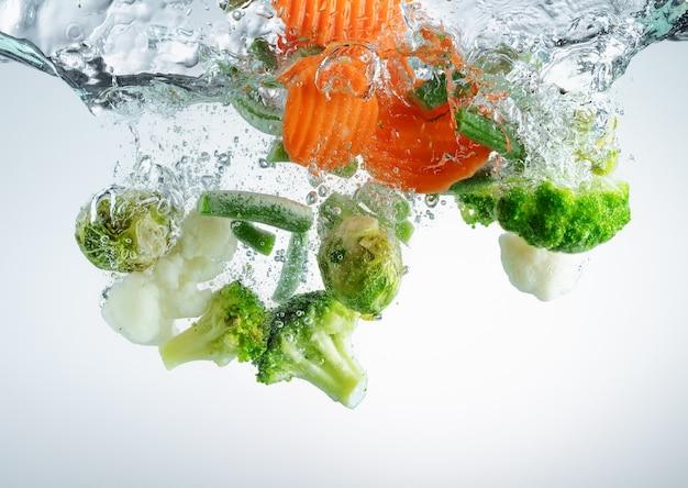 밝아진 및 기포와 함께 물에 떨어지는 야채. 채식 요리.