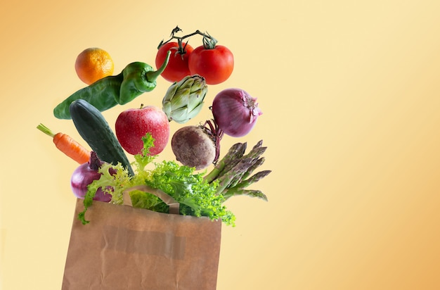 Vegetables flying in recyclable paper bag with copy space