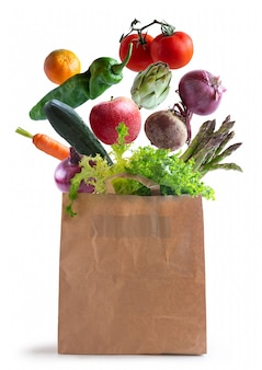 Vegetables flying in recycled paper bag