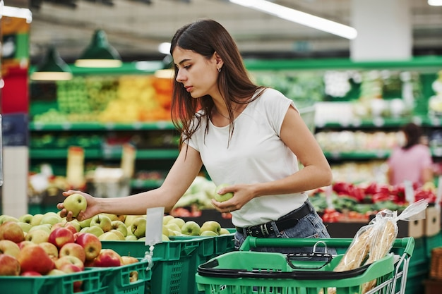 Vegetables and fruits. female shopper in casual clothes in market looking for products.