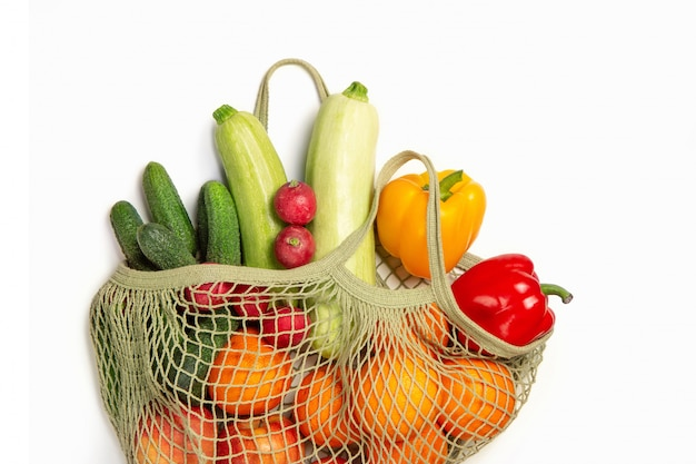 Vegetables and fruits in a string bag on a white isolated background. the concept of green shopping and good nutrition. delivery of products.