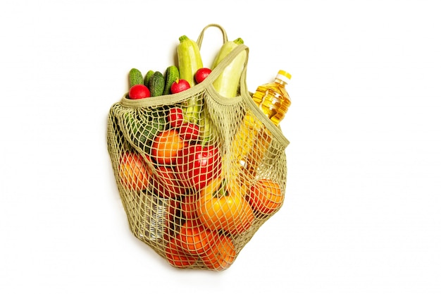 Vegetables, fruits and vegetable oil in a string bag on a white isolated background. the concept of green shopping and good nutrition. delivery of products.