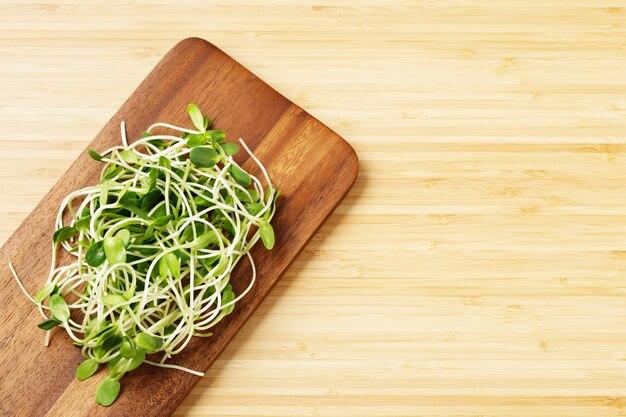 요리된 음식을 위한 그릇에 야채 녹색 신선한 어린 해바라기 콩나물은 영양에 가치가 있습니다. 복사 공간, 나무 테이블에 디자인. 묘목 유기 개념입니다.