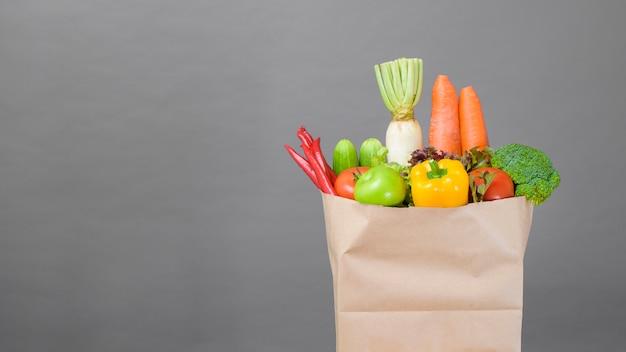 Vegetables in grocery bag on studio grey