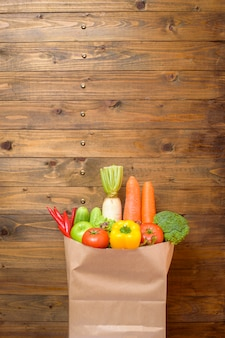 Vegetables in grocery bag on wood background