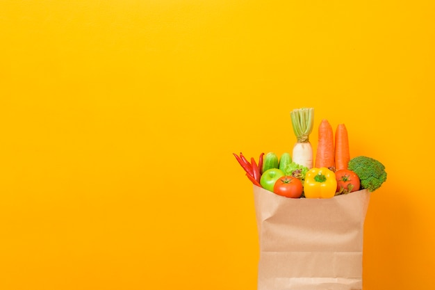 Vegetables in grocery bag on yellow background