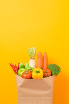Vegetables in grocery bag on yellow wall