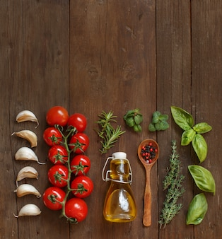 Vegetables, herbs and olive oil on a wooden table, top view, copy space