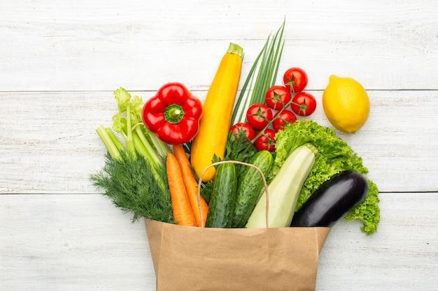 Овощи в бумажном пакете на белой деревянной предпосылке. покупки в супермаркете или на рынке.