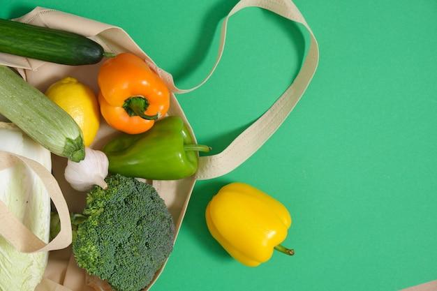 녹색 표면 상위 뷰 제로 폐기물 라이프 스타일 개념에 에코 패브릭 가방에 야채