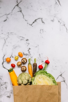 Vegetables in grocery bag against white marble background
