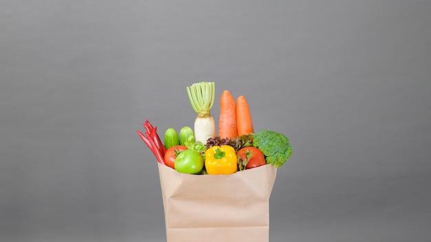 Овощи в продуктовой сумке на сером фоне студии
