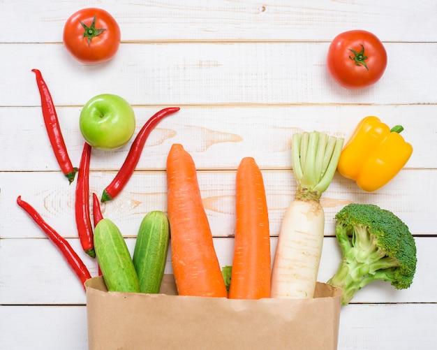白い木製の背景に買い物袋の野菜