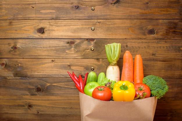 木材の背景に食料品の袋に野菜