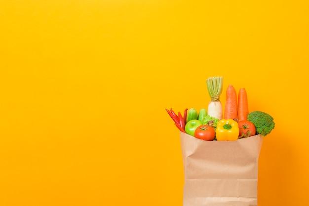 黄色の背景に食料品の袋に野菜