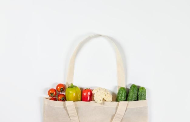 白い背景の上の再利用可能なテキスタイルバッグの野菜