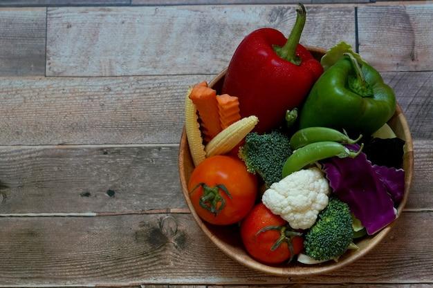 붉은색 피망 당근 아기 옥수수와 같은 나무 배경에 있는 그릇에 야채