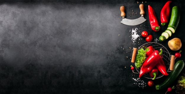 Vegetables and an italian knife placed to the left of a black table