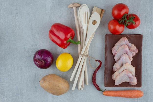 Vegetables, kitchen tools and raw chicken wings on gray surface.