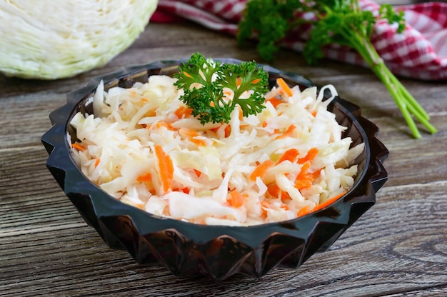 Овощной постный салат из капусты. квашеная капуста в мисках на деревянном столе. витаминное меню. веганская кухня.