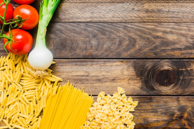Vegetables lying near raw pasta