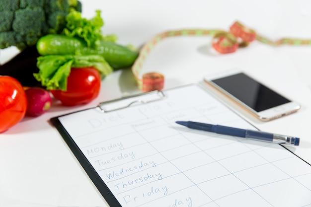 흰색 배경에 분리된 다이어트 계획이 있는 야채, 측정 테이프, 휴대전화, 노트북. 영양사 의사 작업 공간 개념