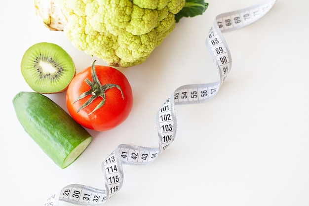 Vegetables and measuring tape on white table.