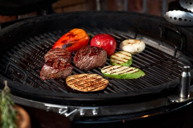 Vegetables and meat sizzling on the grill with flames, close up