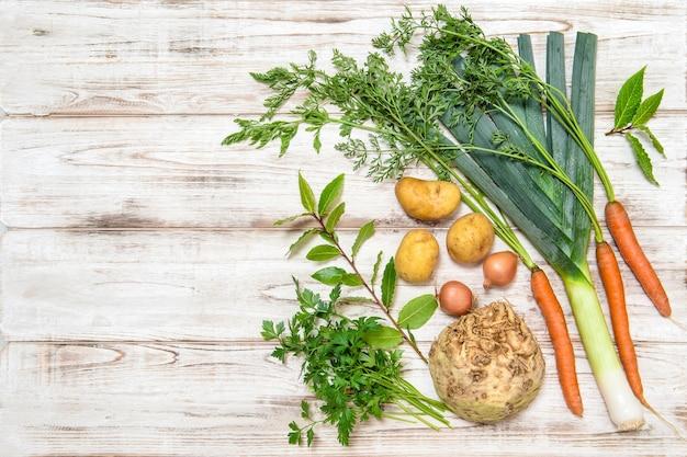 野菜はスープの準備のために混ぜます。リーキ、ニンジン、タマネギ、パセリ、ジャガイモ、セロリの根、月桂樹の葉。健康食品。新鮮な有機栄養