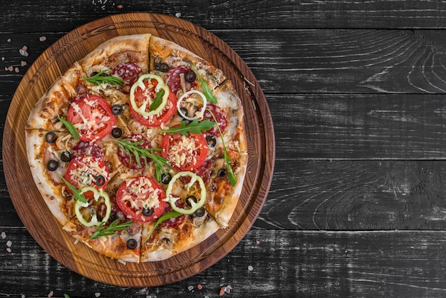 Vegetables, mushrooms and tomatoes pizza on a black wooden background.
