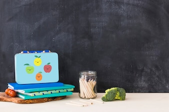 Vegetables near stationery and lunchbox