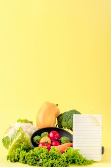 Vegetables and notebook with copy space on yellow background