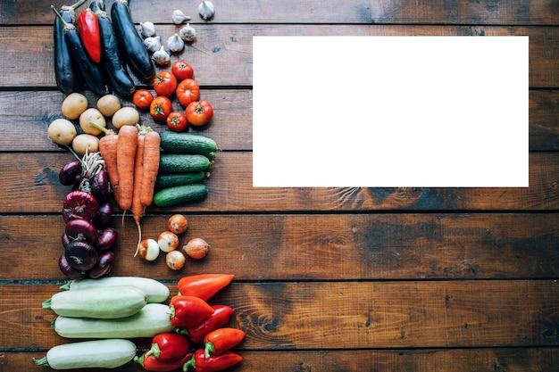 碑文の上面図のための空の場所で暗いテクスチャ背景にさまざまな色の野菜。