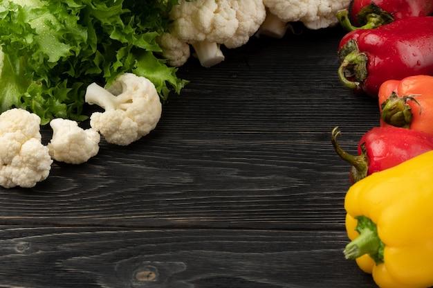 コピースペースと上面図のある暗い木製の背景の野菜