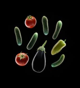 黒の背景に野菜。トマト、ピーマン、キュウリ、ナス。