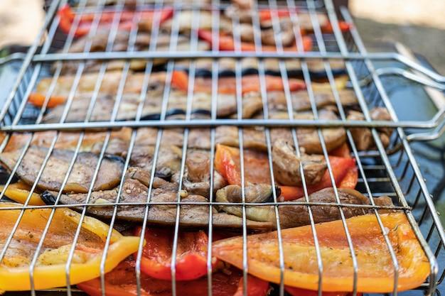 Овощи на гриле крупным планом. на углях обжариваются баклажаны, перец, грибы и чеснок. вегетарианский гриль.