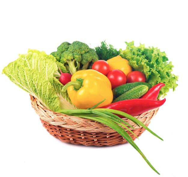 Овощи на белом фоне - брокколи, помидоры, огурцы и зеленый лук. композиция из овощей на белом фоне