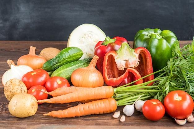 Овощи на деревянных фоне. морковь, красный перец, огурцы, помидоры, чеснок, картофель и лук.