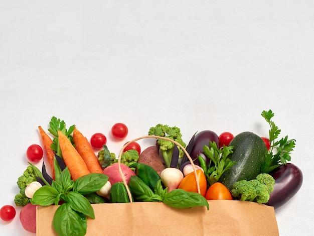 Vegetables in paper bag on white background.