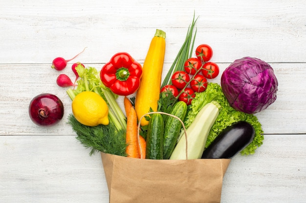 Vegetables in a paper bag on a white wooden background. shopping in a supermarket or market.