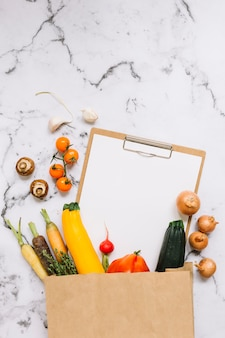 Vegetables and paper on clipboard falling from brown paper bag on marble background