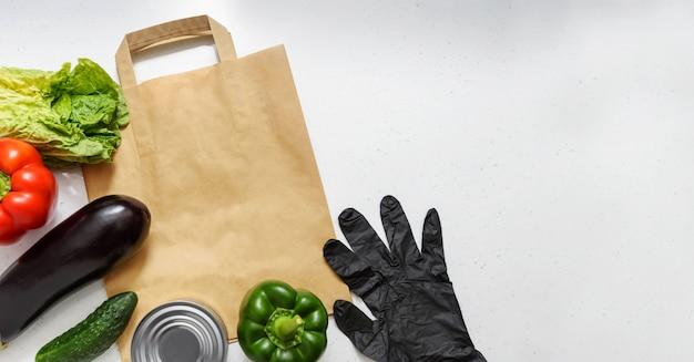 야채, 빨강 및 녹색 고추, 가지, 오이, 통조림 식품, 양상추 및 고무 장갑 격리 된 배경에 종이 봉투에 거짓말. 상위 뷰 복사 공간. 기부. 비접촉식 음식 배달.