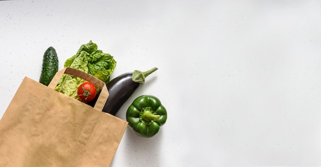 野菜、赤ピーマン、ピーマン、なす、きゅうり、レタス、ゴム手袋が紙袋の上に横たわっています。トップビューコピースペース。寄付。非接触型食品配達。